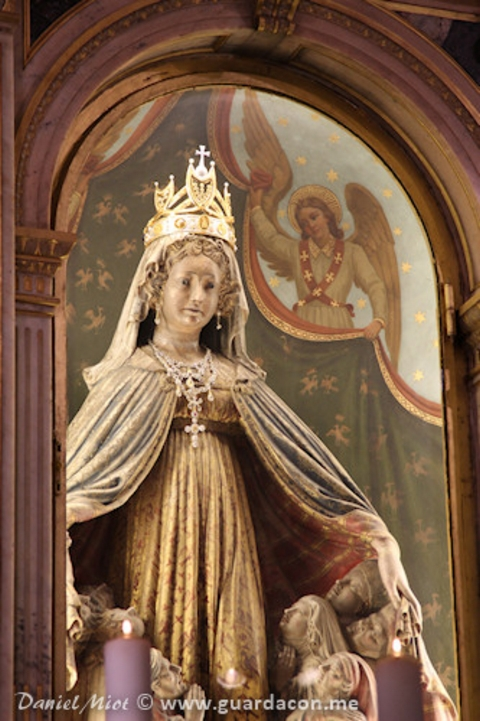 Virgin's statue behind altar in church