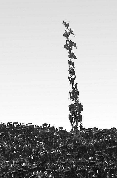 Witnesses precariously climb a tower full of others to get a better view.